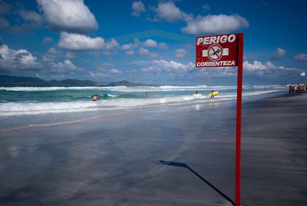 a sign at cabo frio beach in rio de janeiro brazil warns of riptide and not to swim while swimmer and surfers make their way into the water.  a beautiful atlantic ocean sky and beach frame the scenery.