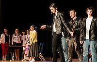 "Danny Zuko (Daniel Kehr) and the Greasers reminisce about ""Summer Nights"" while Sandy Dumbrowski (Olivia Martinson) fills in the Pink Ladies in the background during dress rehearsal for ""Grease"" at Winnisquam Regional High School Thursday afternoon.  (Karen Bobotas/for the Laconia Daily Sun)"