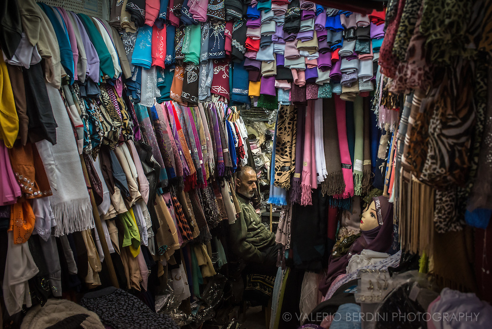 A shop selling dresses and scarves in Old City Jerusalem is packed up with items, the owner has a tiny seat left at the back.