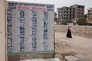 A woman anc child walk past an agency's board listing details of local properties to rent in the village of Bairat, on the West Bank of Luxor, Nile Valley, Egypt.