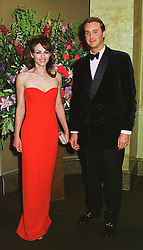 MISS LIZ HURLEY and MR TYRONE PLUNKETT, at a dinner in London on 19th May 1998.MHS 56