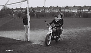 A teenager takes girl for a ride across Ealing sports field on his motorbike. London, Greenford, UK, 1980s.