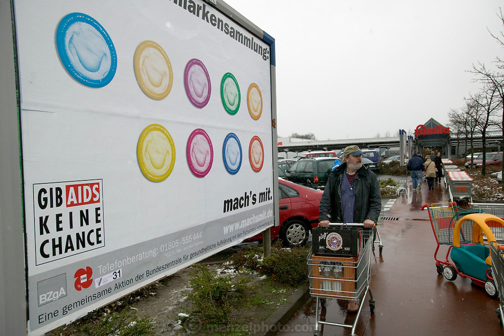 Jörg Melander pushes his shopping cart to his car past an AIDS awareness condom sign at the Famila supermarket in Bargteheide, Germany. (Supporting image from the project Hungry Planet: What the World Eats.)