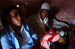 Family and friends sit with un-named 3 day old baby boy, just 3 days after his mother, Kele Tintin,  was caught in the middle of gang warfare and killed on her way to work.  Tintin stayed alive long enough to give birth to a son the same day, and died 6 hours later.    The security situation in Cite-Soleil, one of the most dangerous slums in Haiti,  has deteriorated over the past few months with two warring gangs controlling the entire town.  In Project, the side of town controlled by a pro-aristide gang, the market had to move away from the border zone, people take creaky, wooden boats across the harbor instead of crossing the dividing line, and children are threatened with death if they attempt to cross the line on their way to school.
