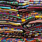 Brightly colored woven textiles are stacked in a market in Antigua Guatemala. Guatemala has a very strong tradition in hand weaving using various types of looms. Famous for its well-preserved Spanish baroque architecture as well as a number of ruins from earthquakes, Antigua Guatemala is a UNESCO World Heritage Site and former capital of Guatemala.