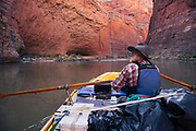 Boatman Thad Stewart approaching Red Wall Cavern in Marble Canyon. Grand Canyon National Park in Arizona.