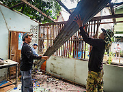 06 OCTOBER 2016 - BANGKOK, THAILAND:  Demolition workers take apart the metal roof of a home in the Pom Mahakan community. Evictions are continuing at a slow pace in Pom Mahakan Fort and as people move out their homes are destroyed to ensure new squatters don't move in. More than 40 families still live in the Pom Mahakan Fort community. Bangkok officials are trying to move them out of the fort and community leaders are barricading themselves in the fort. The residents of the historic fort are joined almost every day by community activists from around Bangkok who support their efforts to stay. City officials said recently that they expect to have the old fort cleared of residents and construction on the new park started by the end of 2016.     PHOTO BY JACK KURTZ