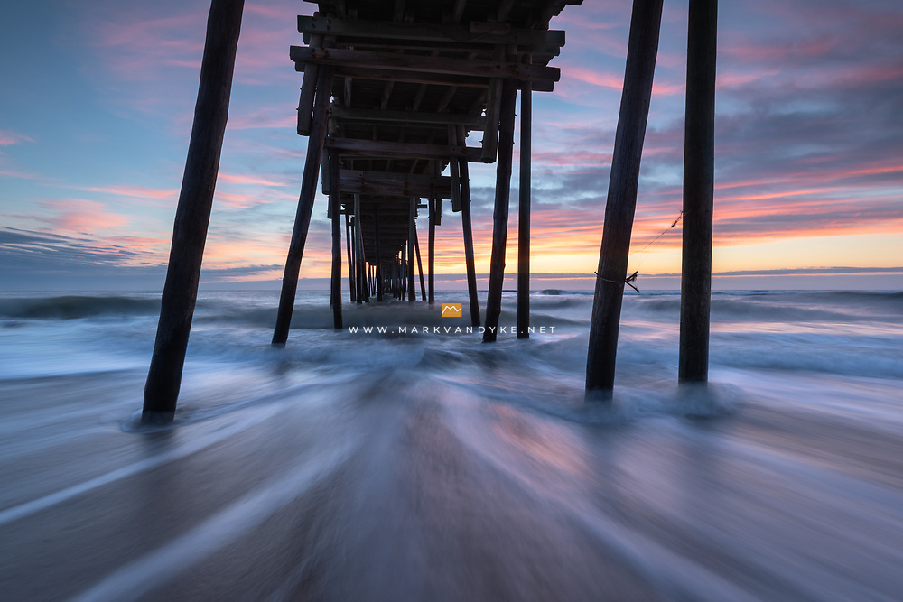 The Avon Fishing Pier in Hatteras, North Carolina was built in the 60's and its rickety wooden structure provides an amazing subject behind the lens!  The Atlantic Ocean rushes beneath, crashing and pulling against the pilings.  In this photo, the subtle hues of predawn provide the backdrop.