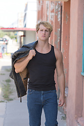 All American blond man in a tank top holding a leather jacket outdoors