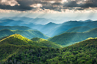 Sunlight punches through thick clouds and onto lush forested Blue Ridge Southern Appalachian Mountains