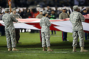 Members of the U.S. Army hold the American flag during pregame ceremonies before the Oakland Raiders NFL week 12 regular season football game against the Kansas City Chiefs on Thursday, Nov. 20, 2014 in Oakland, Calif. The Raiders won their first game of the season 24-20. ©Paul Anthony Spinelli