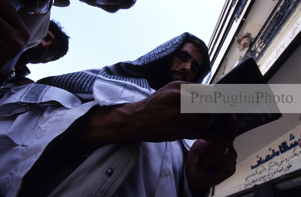 Kabul, 15 August 2005..Undercover Police (?), wearing a mixture of local and westener dress, and an automatic pistol, checking  the passport of suspects on the street.