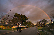 Two women walking dog, Rainbow and storm clouds over suburban street, Pleasant Hill, California