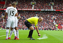 16.08.2014, Old Trafford, Manchester, ENG, Premier League, Manchester United vs Swansea City, 1. Runde, im Bild Referee Mike Dean sprays foam onto the pitch // 15054000 during the English Premier League 1st round match between Manchester United and Swansea City AFC at Old Trafford in Manchester, Great Britain on 2014/08/16. EXPA Pictures &copy; 2014, PhotoCredit: EXPA/ Propagandaphoto/ David Rawcliffe<br /> <br /> *****ATTENTION - OUT of ENG, GBR*****