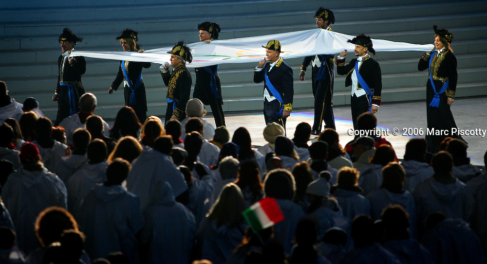 The Olympic Flag is removed from the Stadio Olimpico during the Closing Ceremony for the 2006 Winter Olympics. The ceremony took place Sunday February 26, 2005 at the Stadio Olimpico in Turin, Italy. The Closing Ceremony featured a dizzying array of circus acts, parades and a general carnival atmosphere. Performers included clowns swivelling in large hoops, ballerinas and tumblers, acrobats dangling high above the stage from ribbons and rings, a stilt walker jumping rope, dancers dressed as Tarot cards and highflying acrobats performing over a tunnel of wind. The Closing Ceremony capped off 16 days of Olympic competition that saw the U.S. win 25 total medals, second to only Germany with 29 total medals..(Photo by Marc Piscotty/ © 2006)