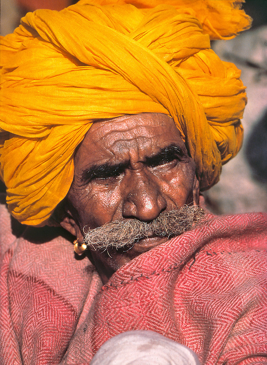 A sun-weathered man in a vivid orange turban squints against the sun at Pushkar Fair, Rajasthan, India.