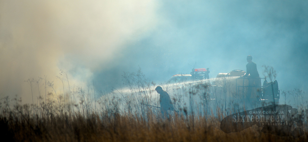 Gary Cosby Jr./Decatur Daily     Firefighters from Danville, Massey and Falkville work to control a fire burning in a sage field along West Lacon Rd. Friday afternoon.  Firefighters work from a brush truck as they extinguish the fire.