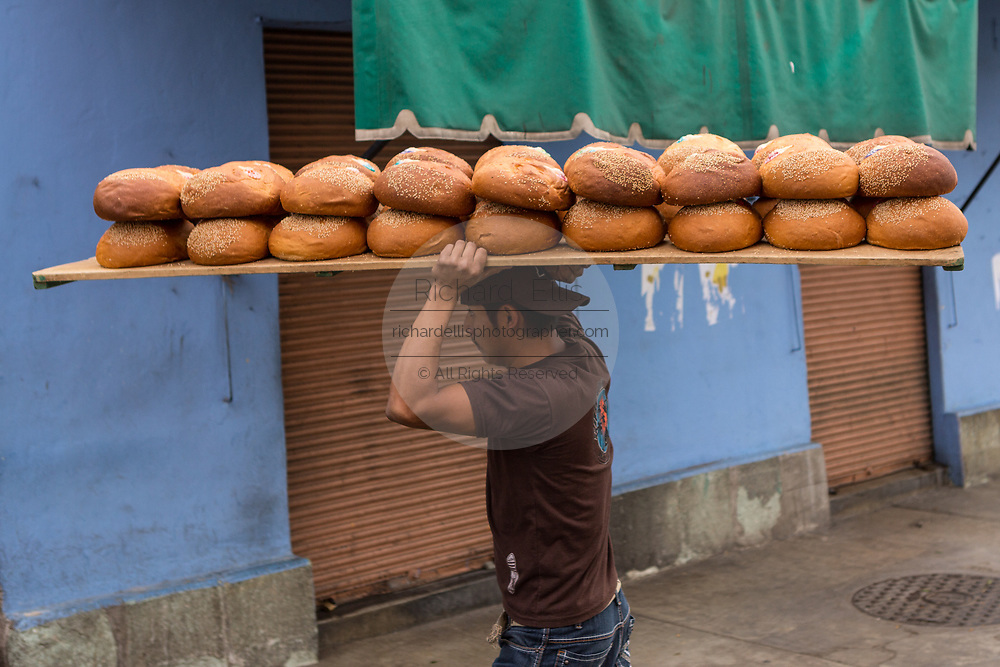 A worker unloads trays of Pan de Muerto a special sweet bread for celebrating the Day of the Dead festival known in spanish as Día de Muertos at Central de Abastos Market October 31, 2013 in Oaxaca, Mexico.