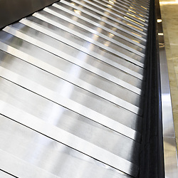 Photo of an airport baggage claim conveyor belt. Photo is high resolution and vertical.