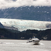 Whale watching boat leaves Auke Bay, Alaska with the Mendenhall Glacier in the background.<br /> Photography by Jose More