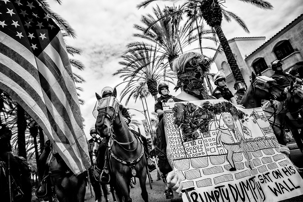 A masked demonstrator carries an Anti-Trump sign with mounted police in tow. Anaheim, Calif. May 26, 2016. (Photo by Gabriel Romero ©2016)