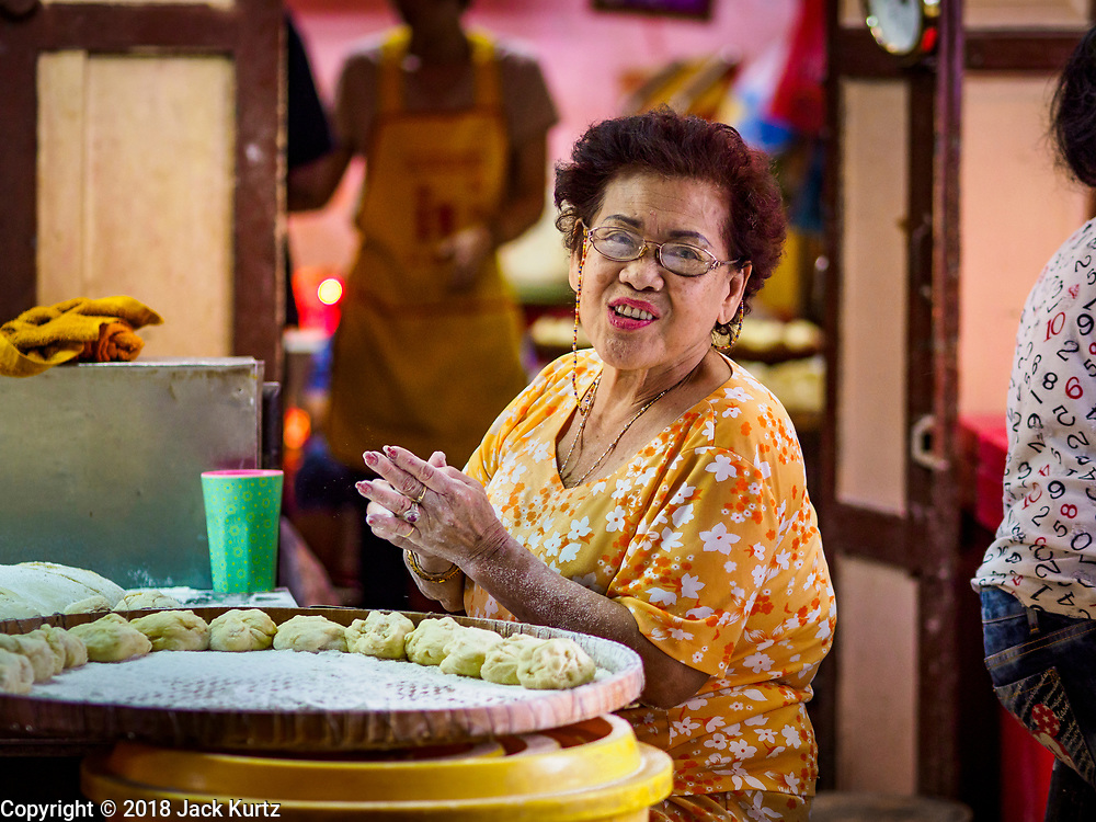 "12 FEBRUARY 2018 - BANGKOK, THAILAND:  A woman hand forms steamed buns in a home that makes steamed Chinese buns, called ""bao"" in the Chinatown neighborhood of Bangkok. Bao are eaten at midnight on the Lunar New Year and served to guests during New Year's entertaining. Lunar New Year, also called Tet or Chinese New Year, is 16 February this year. The coming year will be the Year of the Dog. Thailand has a large Chinese community and Lunar New Year is widely celebrated in Thailand, especially in Bangkok and large cities with significant Chinese communities.   PHOTO BY JACK KURTZ"