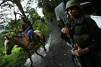A man rides his horse by a patrol of Jungla, a unit of the Colombian anti-narcotics police, while they are searching for a cocaine lab in a remote part of Cundinamarca state in central Colombia, on June 29, 2007. (Photo/Scott Dalton)
