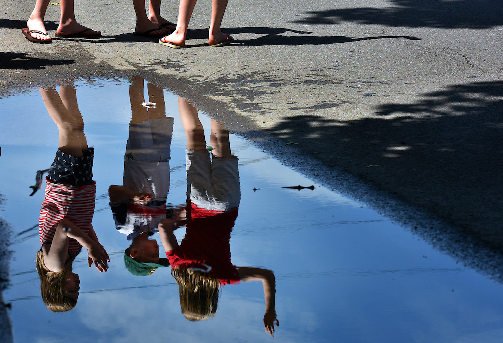 Cate, Benen and Clare Griffin 11, 7 and 9 respectively are reflected in a puddle while they watch and wave at the passing Memorial Day Parade on Wyoming Ave in Forty Fort on Monday afternoon.  A few early morning showers left some puddles but did not deter parade goers. 5/30/2016 Aimee Dilger|Times Leader