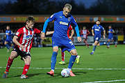 AFC Wimbledon striker Joe Pigott (39) taking on Lincoln City defender Callum Connolly (20) during the EFL Sky Bet League 1 match between AFC Wimbledon and Lincoln City at the Cherry Red Records Stadium, Kingston, England on 2 November 2019.