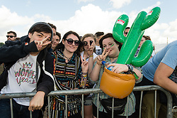 © Licensed to London News Pictures. 28/08/2015. Reading Festival, UK. Festival goers at Reading Festival on Day 1 of the festival queuing waiting for the gates to the arena to open for the first time.  The girl on the right with the inflatable cactus was also first in line last year, when she had an inflatable guitar insteadPhoto credit: Richard Isaac/LNP
