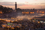 The Place Jemaa-el-Fna, Marrakech, comes to life at dusk. The square is located in the heart of the medina (old city) and overlooked by the minaret of the 12th century Koutoubia mosque. It is one of the largest public squares in the world.  The medina of Marrakech is listed as a UNESCO World Heritage site.