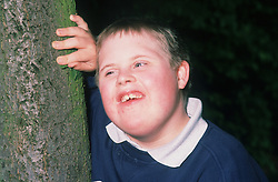 Portrait of young boy with Downs Syndrome smiling,