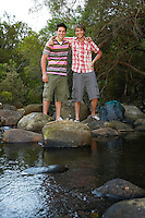 Young Hikers Standing on Rocks by Creek