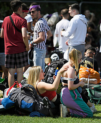 © Licensed to London News Pictures. 21/08/2019. Reading, UK. Two young women apply sun lotion as revelers make their to Reading Festival on a sunny summers day. Warm weather is expected to greet the start of the three day music festival, twinned with Leeds Festival, which attract over 90,000 people over the bank holiday weekend. Photo credit: Ben Cawthra/LNP