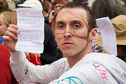 London, UK. 23rd April 2019. A climate change activist from Extinction Rebellion in Parliament Square holds up a letter to Theresa Villiers, his Member of Parliament, imploring her to take action to prevent climate change. Activists tried to deliver their letters to Parliament, but all but ten were prevented from doing so by the Metropolitan Police.