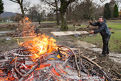 © Licensed to London News Pictures. 11/12/2015. Keswick UK. Jimmy Little throws floorboards from Keswick Football Club on to a fire after the club house was flooded earlier this week. Photo credit: Andrew McCaren/LNP