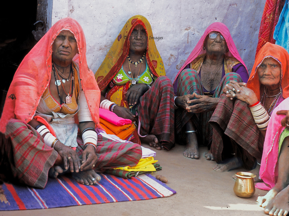 Four elderly Rajasthani women in their best traditional dress seated on the ground looking at the camera.