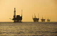 A line of off shore oil rigs at sunset in the Santa Barbara Channel, California, USA.