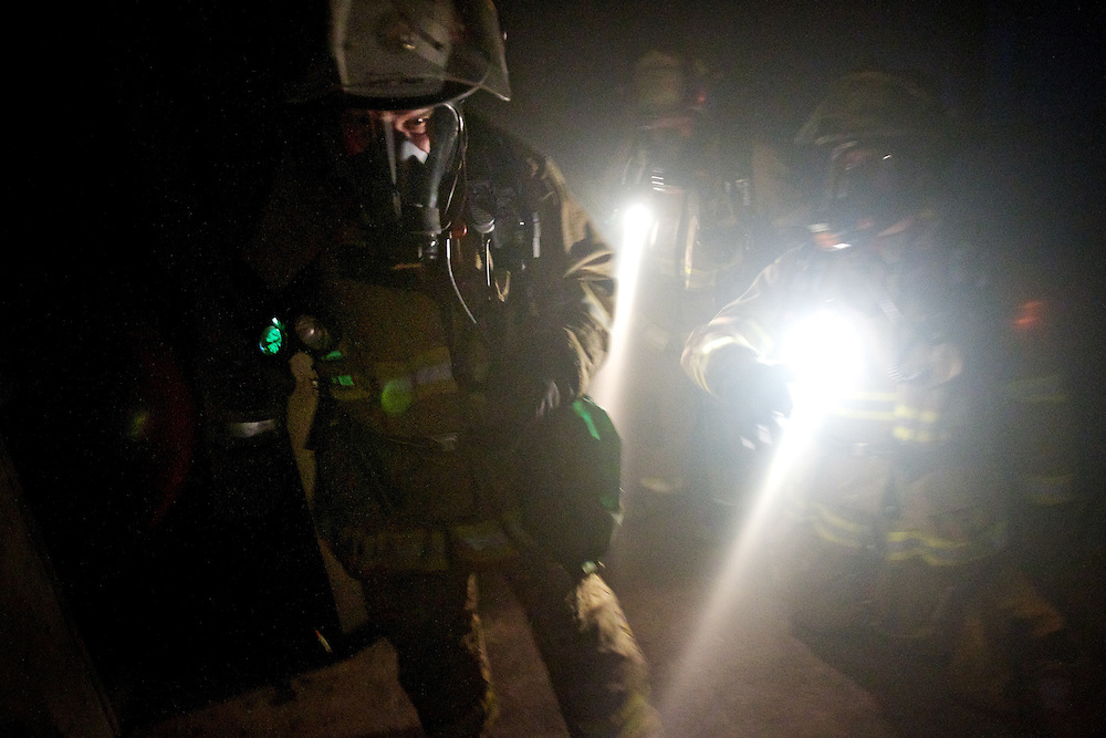 Coeur d'Alene firefighters explore a darkened, smoke-filled room during a search-and-rescue exercise July 28 at the Coeur d'Alene Fire Department training facility.
