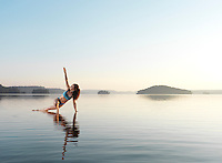 Young woman practicing Hatha yoga on a floating platform in water on the lake in early morning. Yoga, a variation of Triangle pose, Trikonasana. Muskoka, Ontario, Canada.