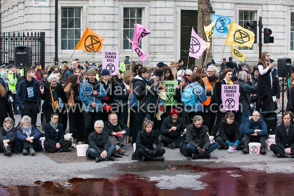 London, UK. 9th March, 2019. Climate activists from Extinction Rebellion pour artificial blood on the ground outside Downing Street as part of an act of civil disobedience named 'The Blood of Our Children' to call on the Government to take immediate steps to combat the current climate and ecological emergency.