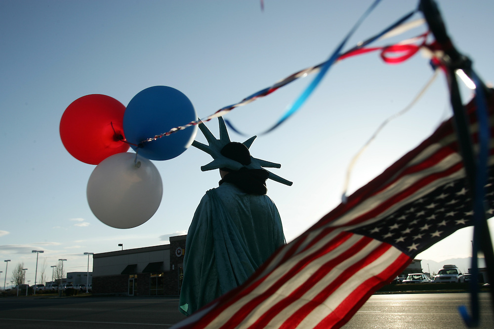 photography / Troy Boman.Dressed up as the Statue of Liberty, Cole Manzanares waves to passing traffic on Tooele's Main St. Wednesday.