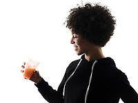 one mixed race african young teenager girl woman drinking orange juice  in studio shadow silhouette isolated on white background