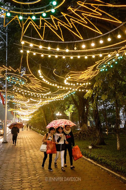 School girls walk under lights strung for the Tet celebration around Hoan Keim Lake on a rainy night in Hanoi.