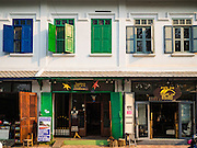 "11 MARCH 2016 - LUANG PRABANG, LAOS:  A colonial style shophouse turned into tourists' boutiques and souvenir shops in Luang Prabang. Luang Prabang was named a UNESCO World Heritage Site in 1995. The move saved the city's colonial architecture but the explosion of mass tourism has taken a toll on the city's soul. According to one recent study, a small plot of land that sold for $8,000 three years ago now goes for $120,000. Many longtime residents are selling their homes and moving to small developments around the city. The old homes are then converted to guesthouses, restaurants and spas. The city is famous for the morning ""tak bat,"" or monks' morning alms rounds. Every morning hundreds of Buddhist monks come out before dawn and walk in a silent procession through the city accepting alms from residents. Now, most of the people presenting alms to the monks are tourists, since so many Lao people have moved outside of the city center. About 50,000 people are thought to live in the Luang Prabang area, the city received more than 530,000 tourists in 2014.      PHOTO BY JACK KURTZ"