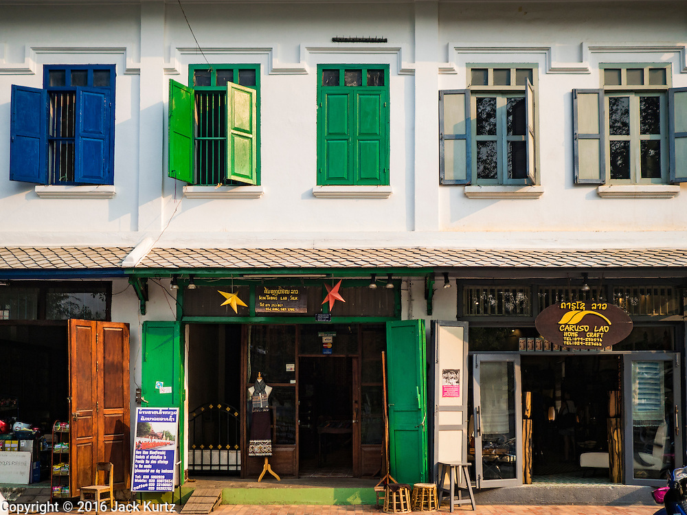"""11 MARCH 2016 - LUANG PRABANG, LAOS:  A colonial style shophouse turned into tourists' boutiques and souvenir shops in Luang Prabang. Luang Prabang was named a UNESCO World Heritage Site in 1995. The move saved the city's colonial architecture but the explosion of mass tourism has taken a toll on the city's soul. According to one recent study, a small plot of land that sold for $8,000 three years ago now goes for $120,000. Many longtime residents are selling their homes and moving to small developments around the city. The old homes are then converted to guesthouses, restaurants and spas. The city is famous for the morning """"tak bat,"""" or monks' morning alms rounds. Every morning hundreds of Buddhist monks come out before dawn and walk in a silent procession through the city accepting alms from residents. Now, most of the people presenting alms to the monks are tourists, since so many Lao people have moved outside of the city center. About 50,000 people are thought to live in the Luang Prabang area, the city received more than 530,000 tourists in 2014.      PHOTO BY JACK KURTZ"""