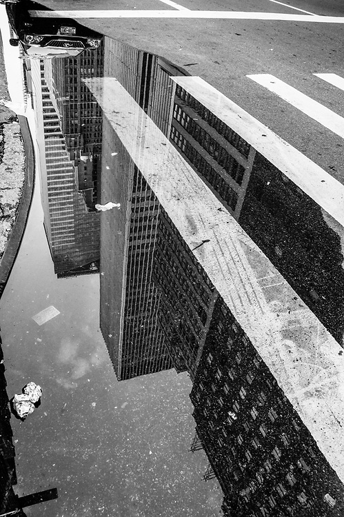Curbside reflection of car and buildings in nyc. 2011