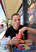 An 18-year-old male eats fast food.