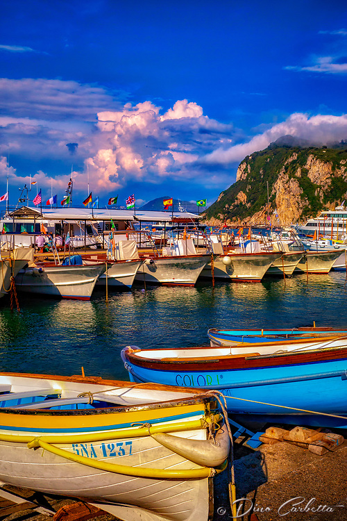 """""""The colors of Capri""""…<br /> <br /> On the third morning in Sorrento, I departed on a high speed Ferry to the island of Capri.  Although promoting high-speed, it still took over an hour to arrive at the very crowded Island.  Capri is located off the coast of Naples and there must be a new Ferry full of tourists arriving every 20 minutes throughout the day.  Famous for its Blue Grotto, which I did not venture to this trip, Capri is a picturesque Mediterranean retreat with high cliffs and ancient Roman villas. The highlight of my visit was the small and very crowded bus ride along the cliffs edge to Anacapri.  I was standing closest to the door on the right side of the bus during the assent up the mountainside.  All I could see was the rocky shore below and with every leaning left turn, prayed desperately I would make it to the top.  Anacapri is a historic mountaintop town with commanding views of Capri and the sea below.  This image was taken in the Bay of Capri while waiting for the last Ferry back to Sorrento.  My eye caught the color of the blue boat and it was the same color of the late afternoon sky.  Ironically, the name on the side of the little boat was """"colori""""…meaning colors."""