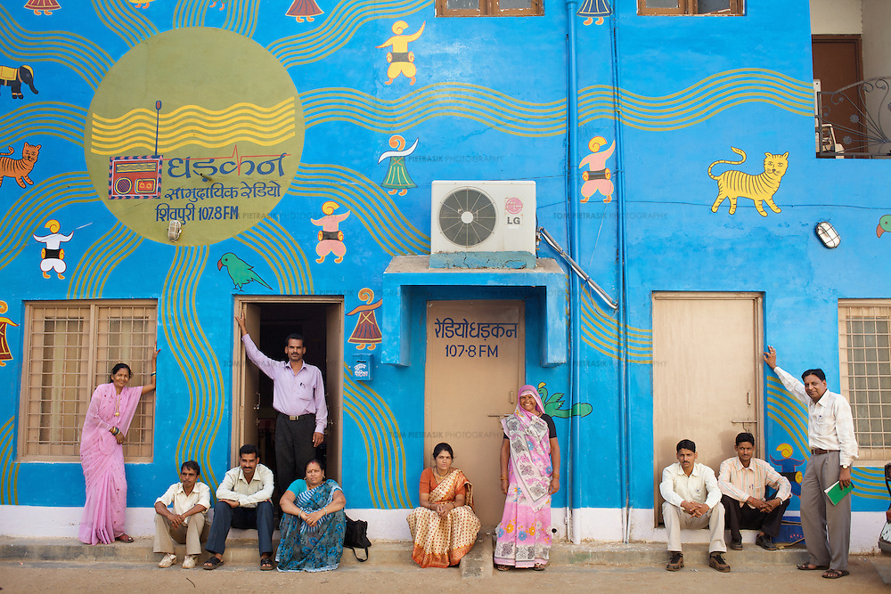 The staff of Dharkan 107.8 including station manager Vandana Dube (in brown sari) and program maker Ramvati Adivasi (in pink sari, centre) outside the station offices in Shivpuri. Before the official launch of the community radio station in July 2009, Vandana and her colleagues have recorded several programs informing women of government health services. As well as her role at Dharkan 107.8, Adivasi is is an ASHA (local female health advisor). She provides a free referral service to local women, keeping them in touch with government health services. Adivasi receives a fee from the government for every referral. This is one means by which the government and partners UNICEF are increasing the rate of institutional deliveries in Madhya Pradesh state. Adivasi has recorded several programs informing women of government health services. ..Shivpuri district in Madhya Pradesh suffers from poor health outcomes. Of particular concern is the high rate of maternal mortality. One of the Indian government's aims, with partners Unicef, is to encourage the population to adopt practices to improve sanitation and health practices. In an area made up of traditionally disadvantage groups and suffering low literacy rates, this can be a challenge. ..A survey found that radio was the most readily accessible media by the Shivpuri community with more than half saying they tuned in several times a day. ..Dharkan 107.8 FM will go on air in July. The station that will broadcast to 75 villages in a 15-kilometer radius reaching 170,000 people...Rather than preaching educational messages, the station, which is already producing pilot programs, uses humor and folk artists performing in the local language to entertain and inform their audiences. There is a major impact, especially on women, who are contributing their voices to such wide-ranging issues as caste discrimination, female feticide and women,A?o?s empowerment. ..Photo: Tom Pietrasik.Shivpuri, Madhya Pradeh. India.June 2009